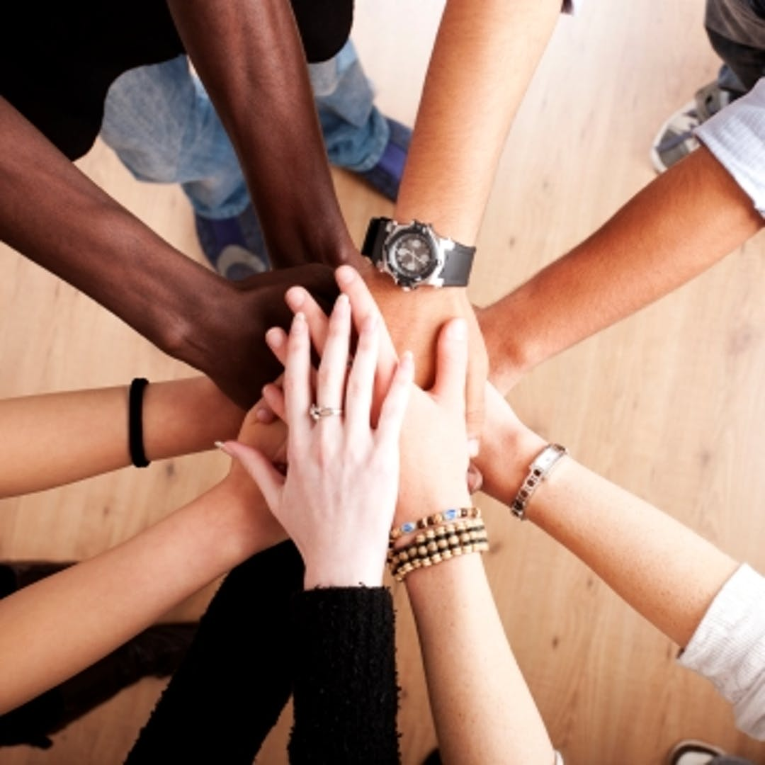 Picture of a circle of hands on top of one another