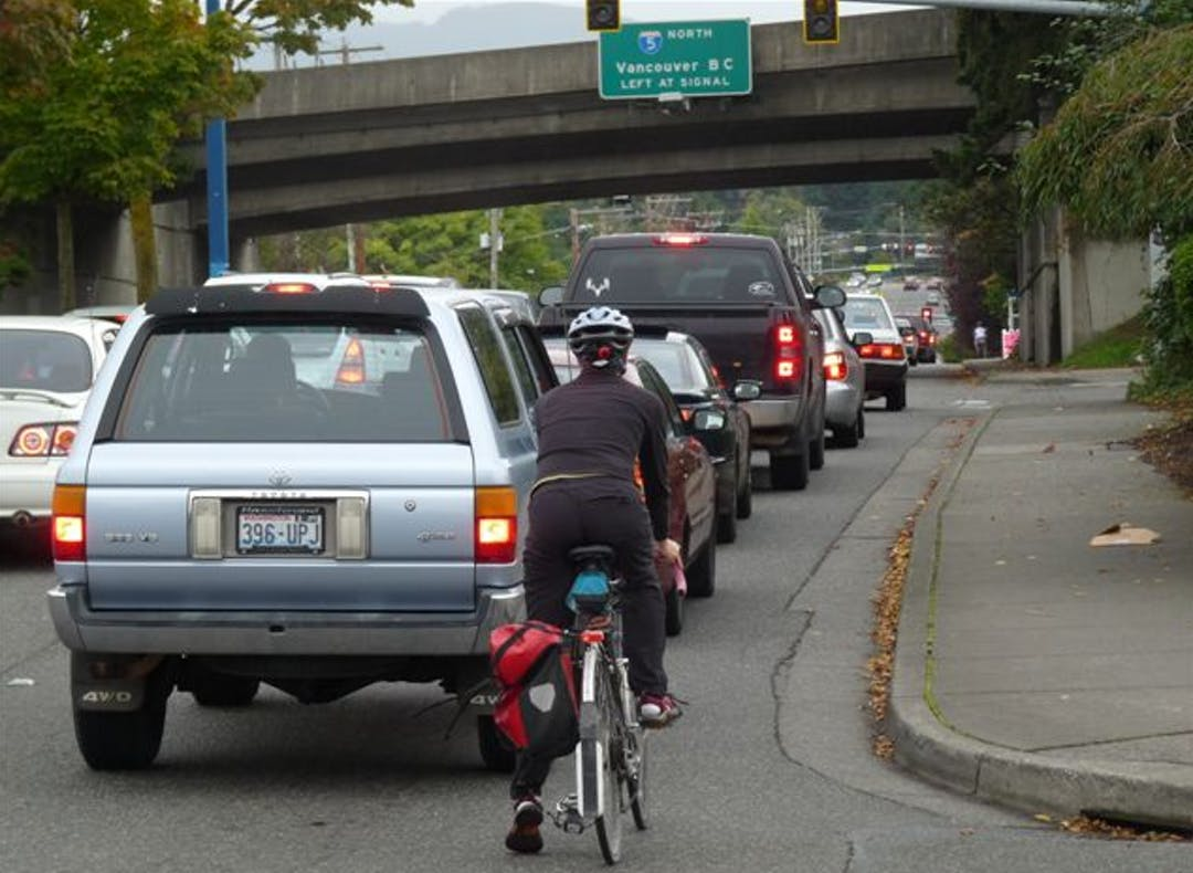 Biker riding on Lakeway Drive with vehicles at the Interstate 5 southbound on-ramp