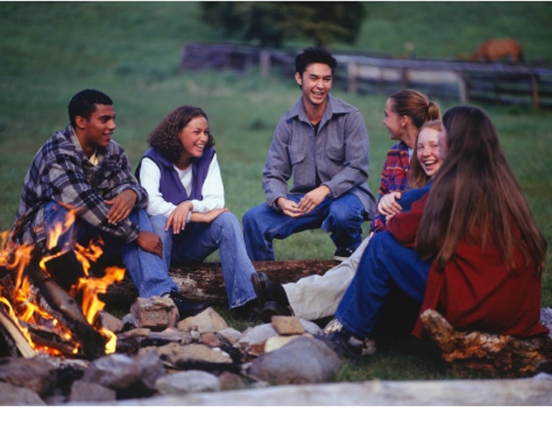 People telling a story around the campfire.