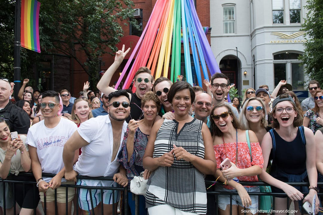 Group of 2019 Capital Pride Parade attendees posing for a photo with Mayor Muriel Bowser with the Rainbow Pride Flag in the back