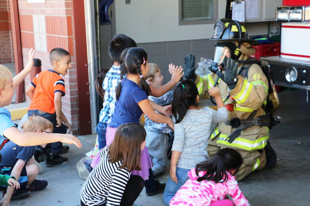 This image shows a fully-outfitted firefighter interacting with young children.