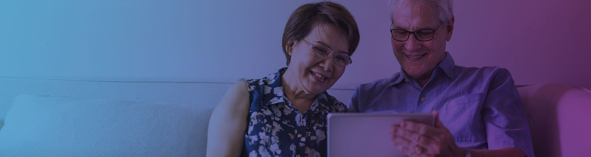 pink and purple gradient with a senior couple looking at a computer together
