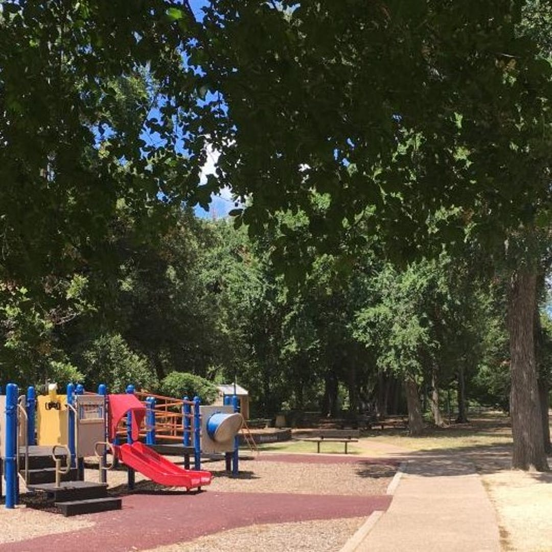 Image of playground with some of the surrounding sidewalk and area trees at Beverly S. Sheffield District Park