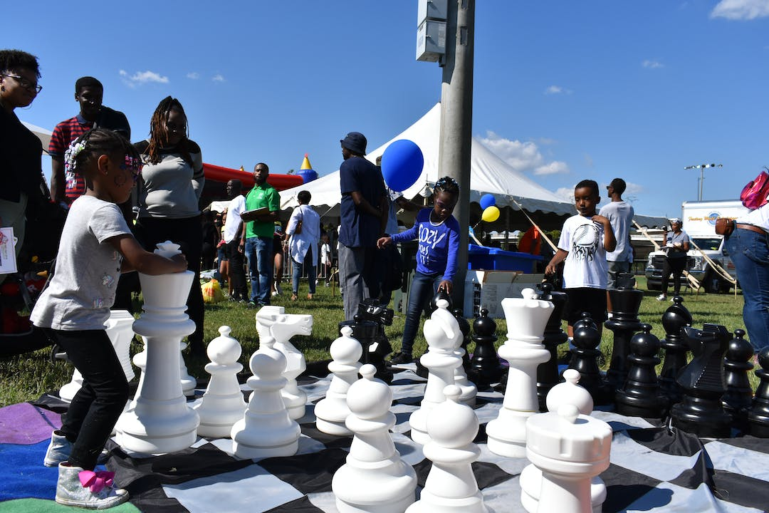 Children playing with giant chess set
