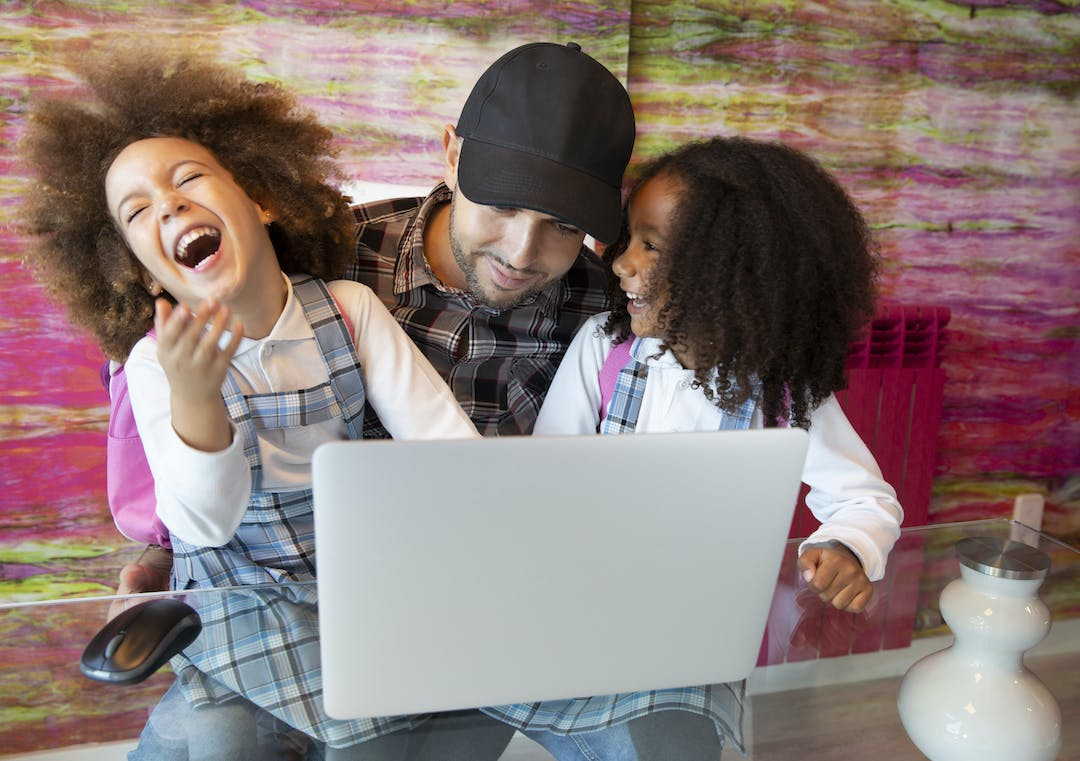 Dad looking at the internet on a computer while his two daughters laugh.