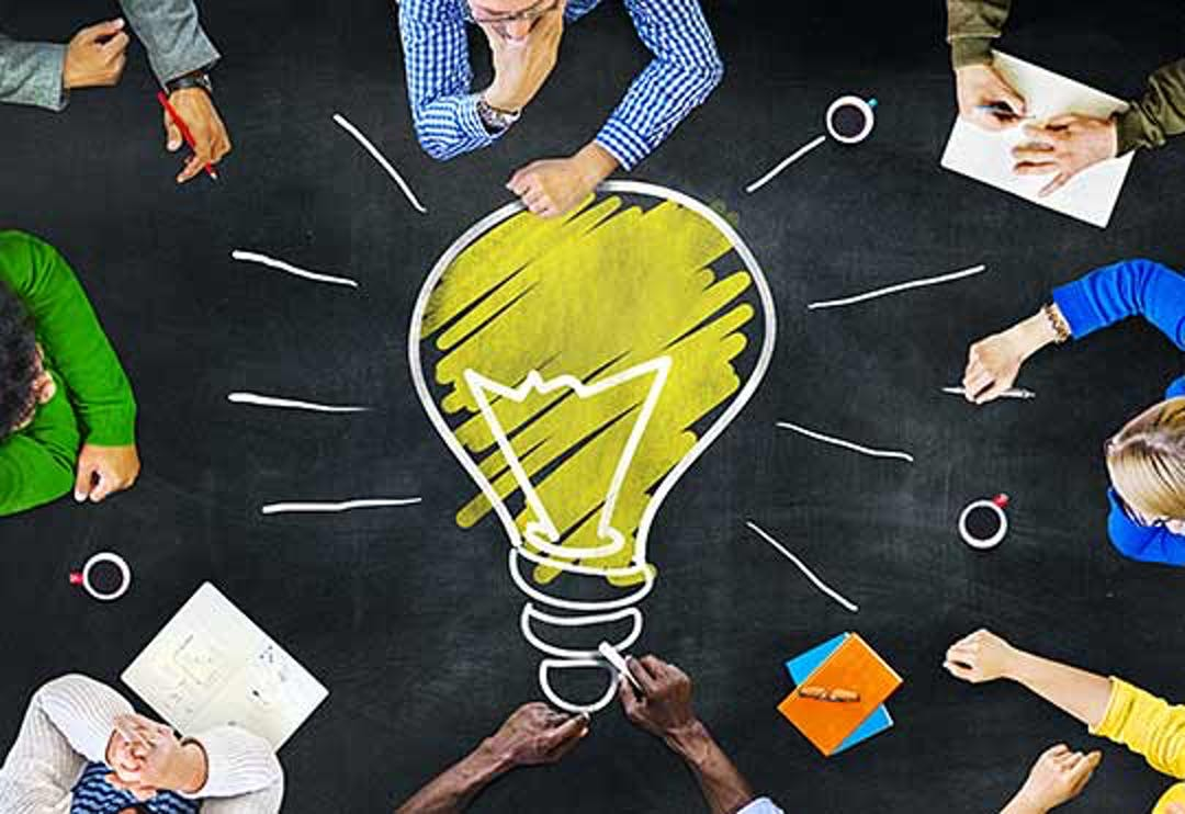 Group of people gathered around the image of light bulb.