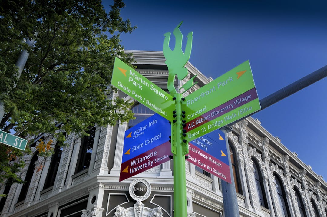 Wayfinding sign in downtown Salem with arrows directing visitors to Willamette University, state capitol, Marion square park, riverfront park, and other sights with a backdrop of the Ladd Bush bank