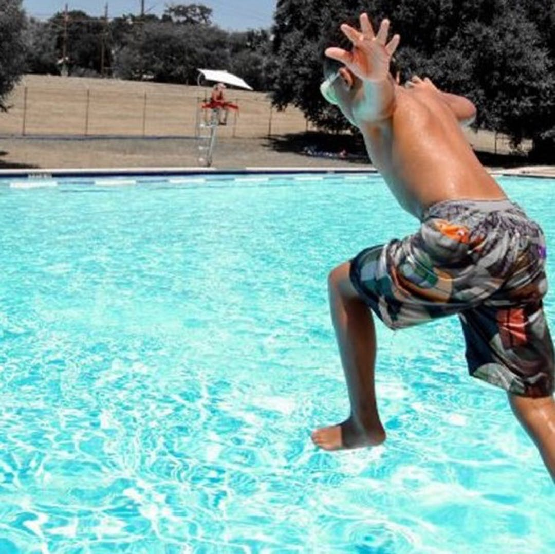 Image of kid jumping into a swimming pool