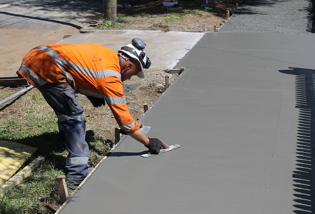 A Public Works maintenance worker levels concrete as part of walkway resurfacing.