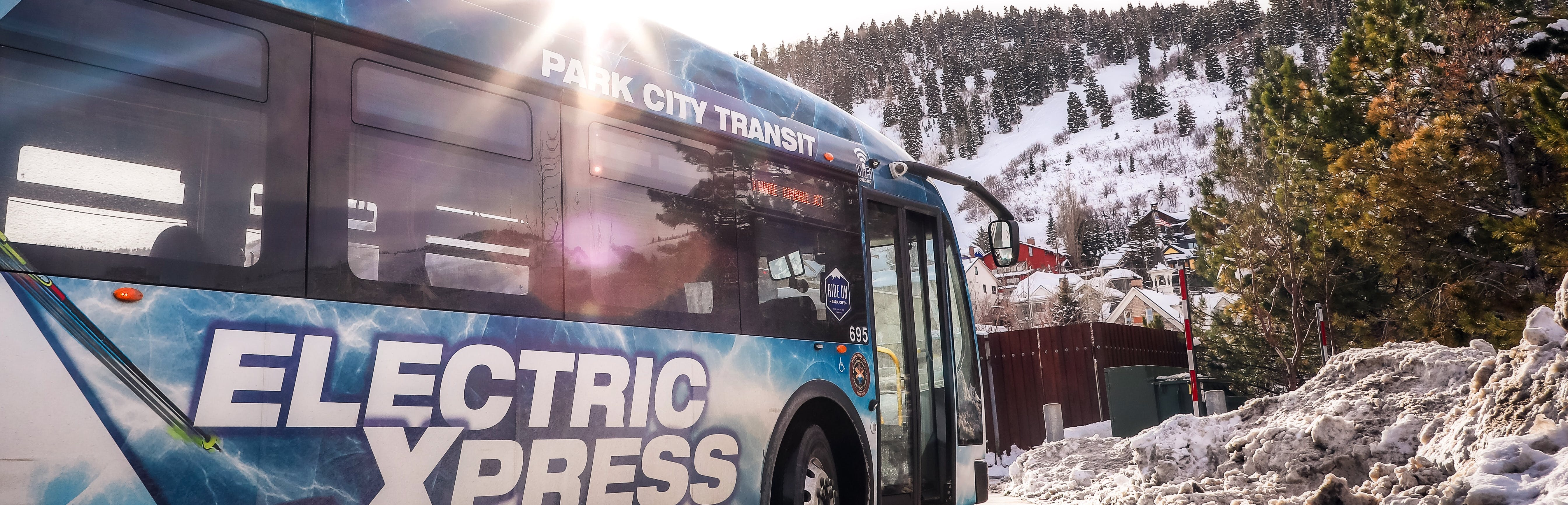 Image depicts a Park City Transit bus parked at a curb, surrounded by snow.