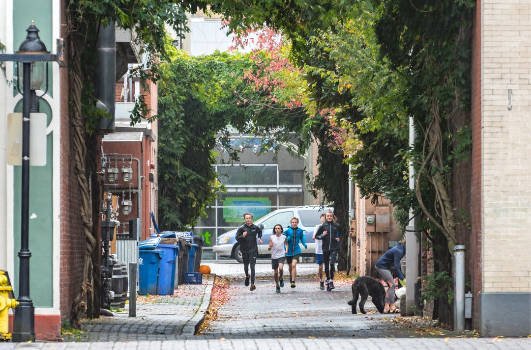 Group of children run toward camera down an alley with an old fashioned light post, trees in the background, dog in the alleyway