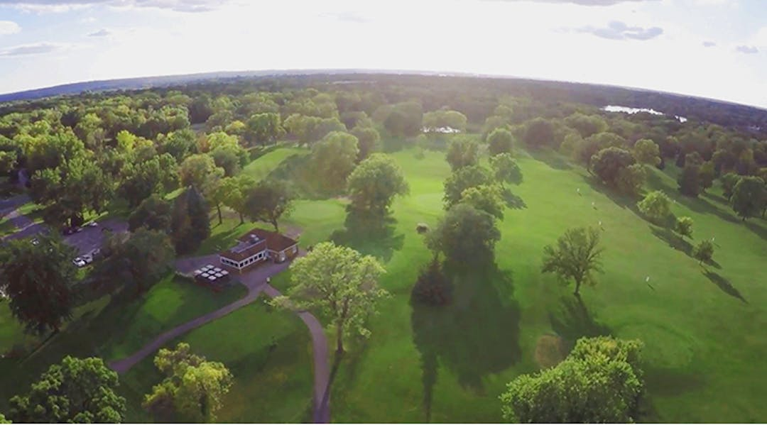 An aerial shot of Hyland Greens with clubhouse, driving range, and horizon.