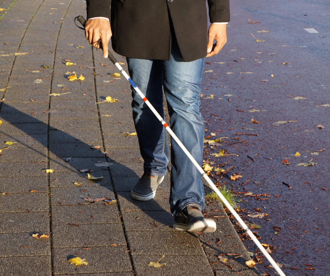 Lower half of a person walking down a sidewalk with an assistive device.