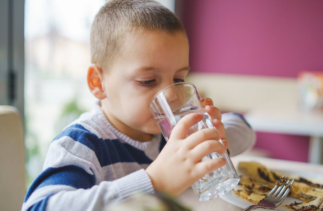 A boy drinks water from a glass at a restaurant.