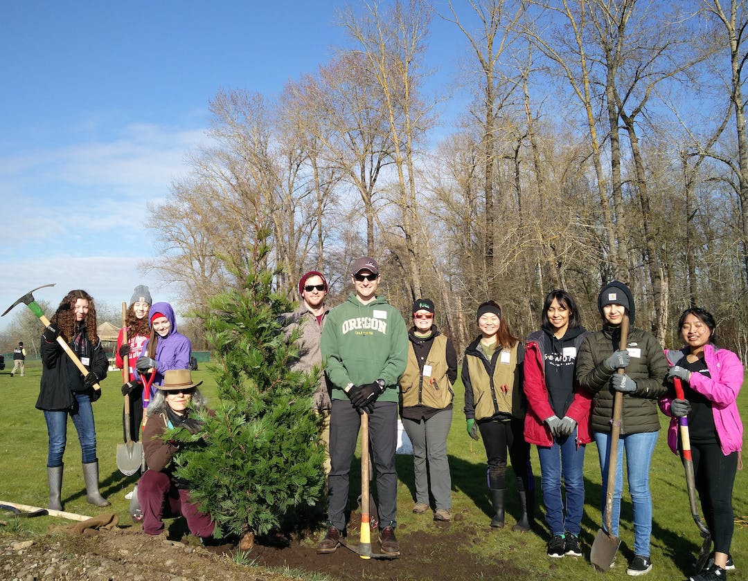 Group of 10 community members standing next to a tree they planted with various tools