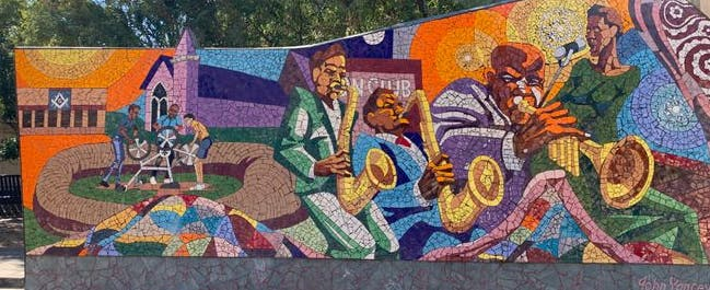 """Photo of """"Rhapsody"""" an outdoor mosaic tile mural by John Yancey on East 11th Street in Austin, Texas."""