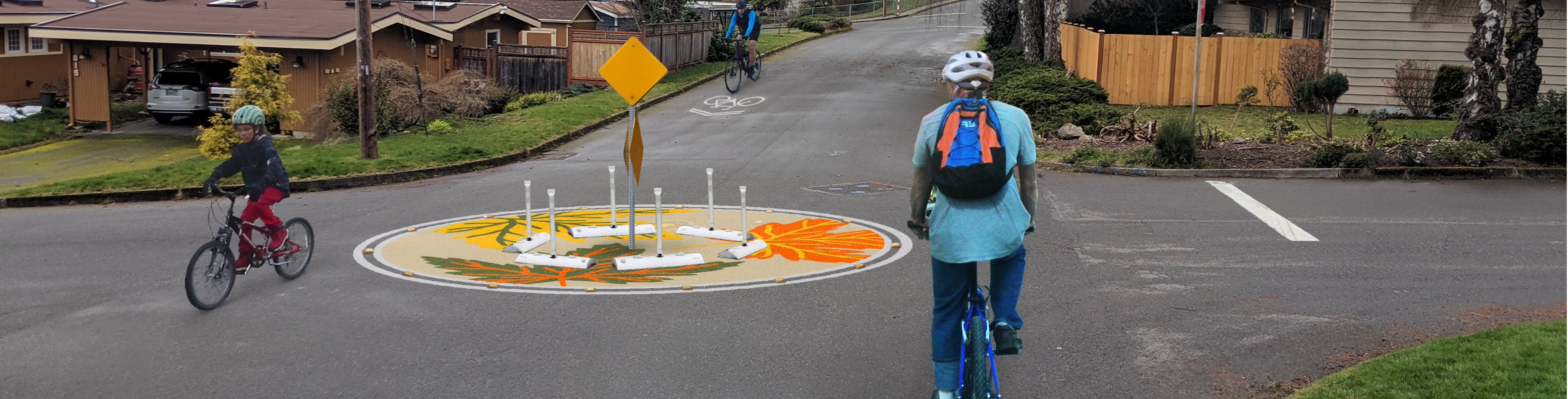 Three people riding bicycles on a street with the proposed decorative traffic circle treatment.