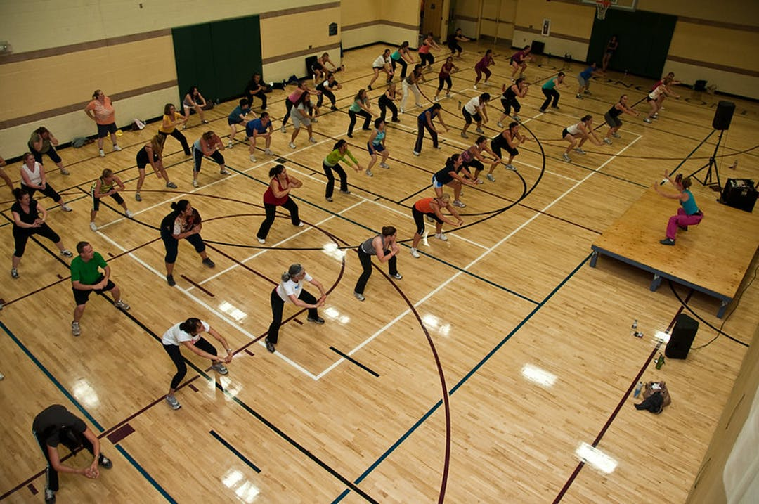 A group of people participate in a group exercise class in the gym