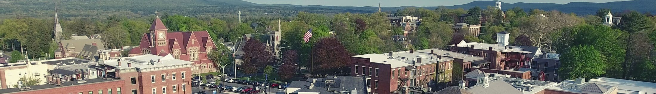 Aerial view of Downtown Amherst Massachusetts with brick buildings and green trees and hills in the background.