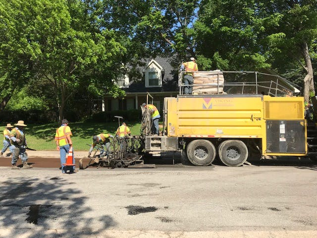 Street maintenance crew makes repairs on asphalt street.