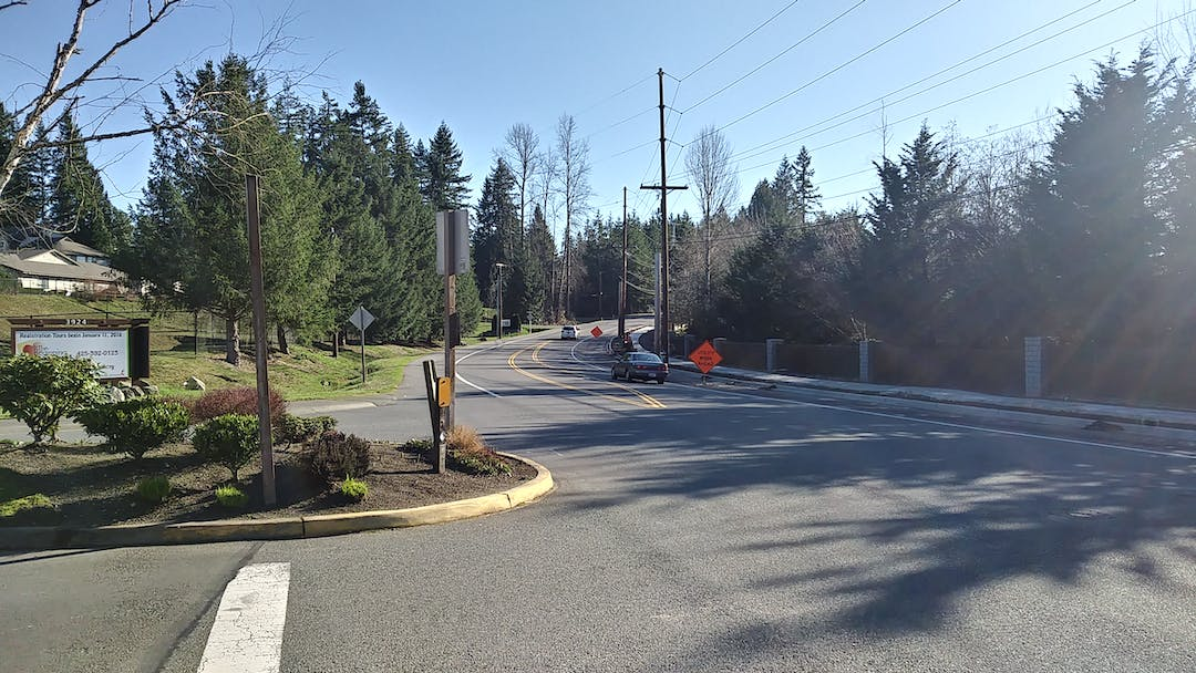 Photo of a section of Issaquah-Pine Lake Road with two cars driving past an intersection, on a sunny day.