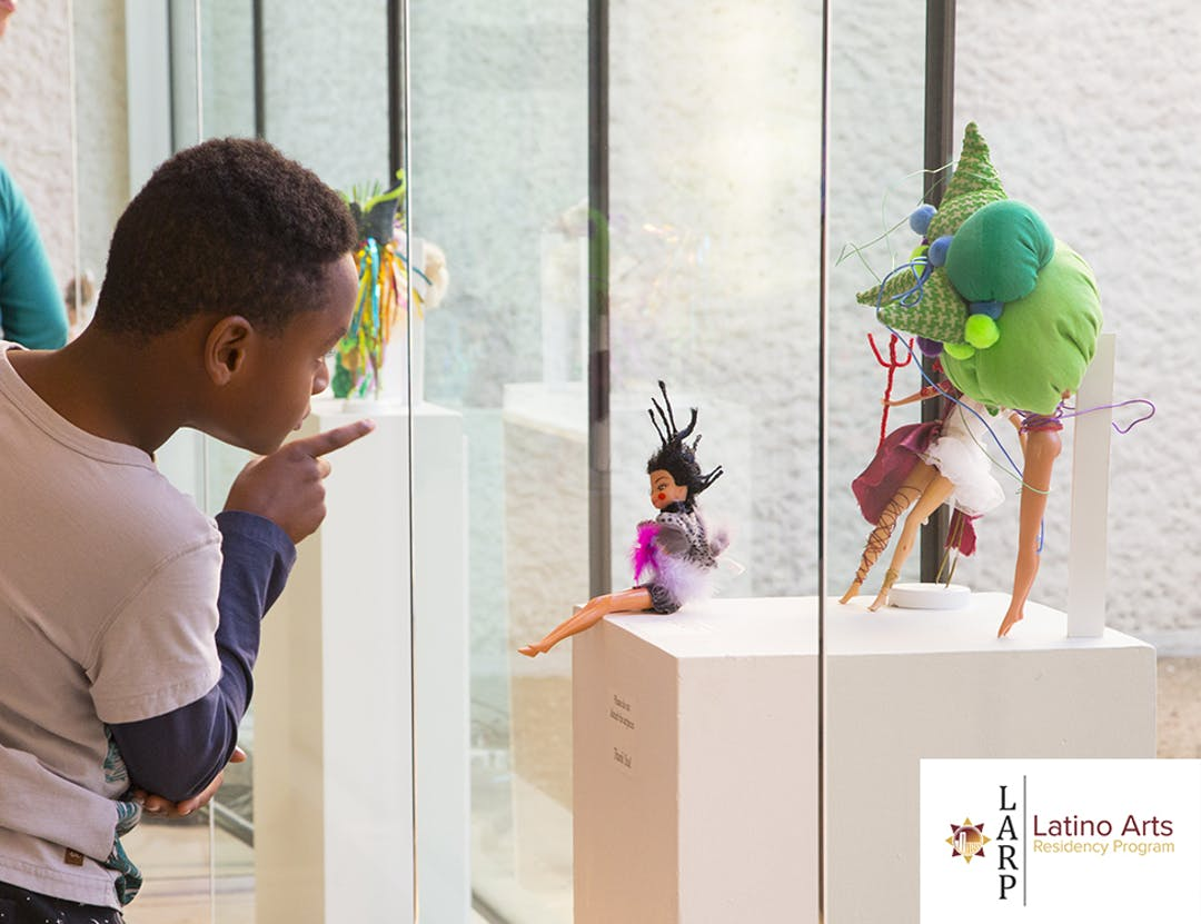 The image shows a young boy leaning in for a closer look at one of the pieces from April Garcia's Bizarbie work on display at the ESB-MACC.