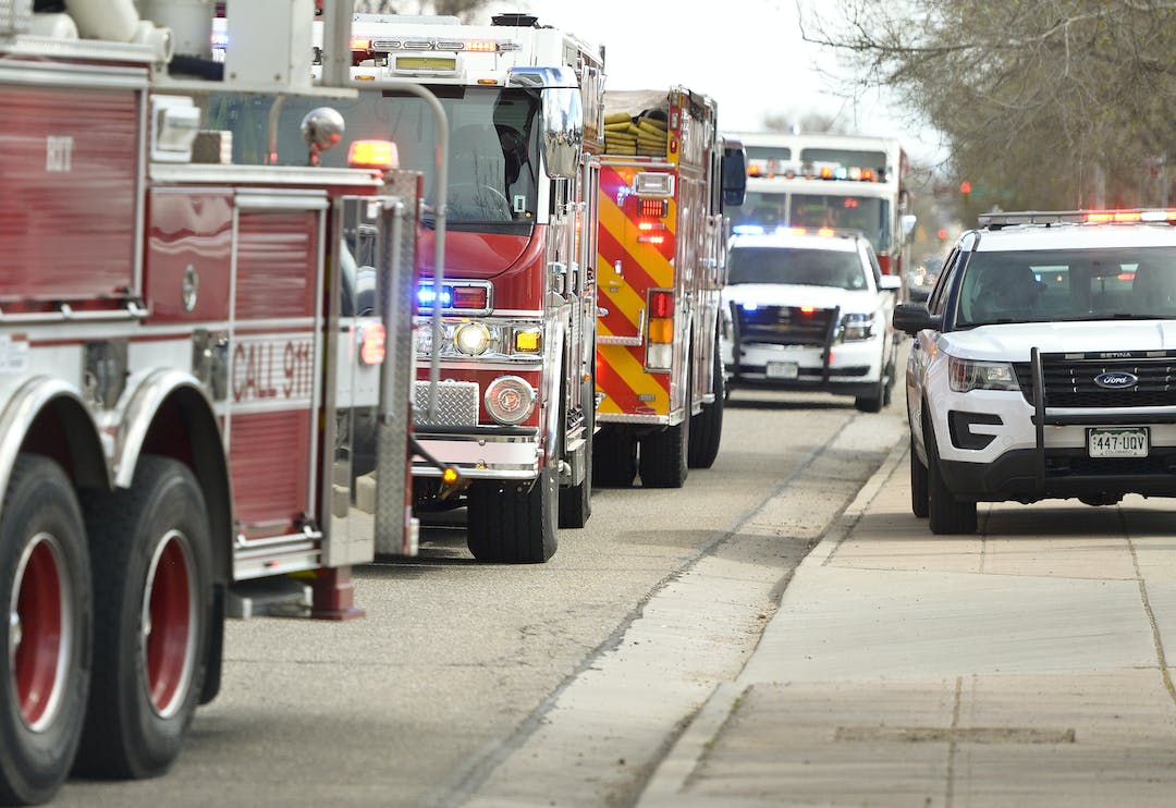 Police cars and fire trucks flash lights while at a scene of a crash. Photo taken by Times-Call photographer Matthew Jonas.