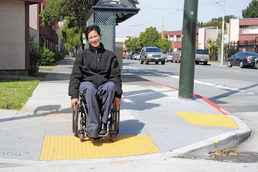 A middle aged woman with dark hair and dark clothing using a wheelchair to cross from a marked curb ramp into the street