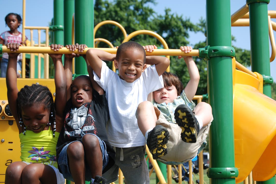 Four children balancing in a monkey bar of a DC's playground