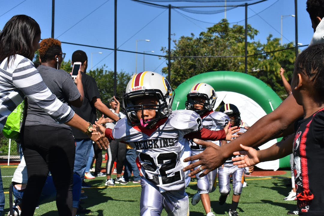 Players from the DPR's Youth Tackle Football team catching high fives from their family members and friends