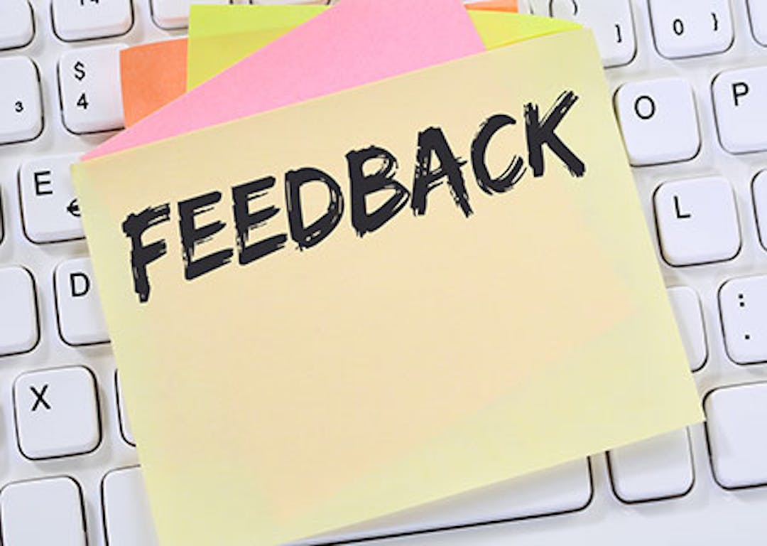 "A sticky note that says ""feedback"" which is laid atop a keyboard."