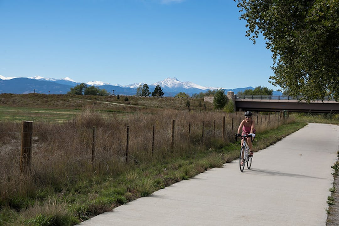 Woman rides bicycle on trail with grass, mountains and bridge in the background.