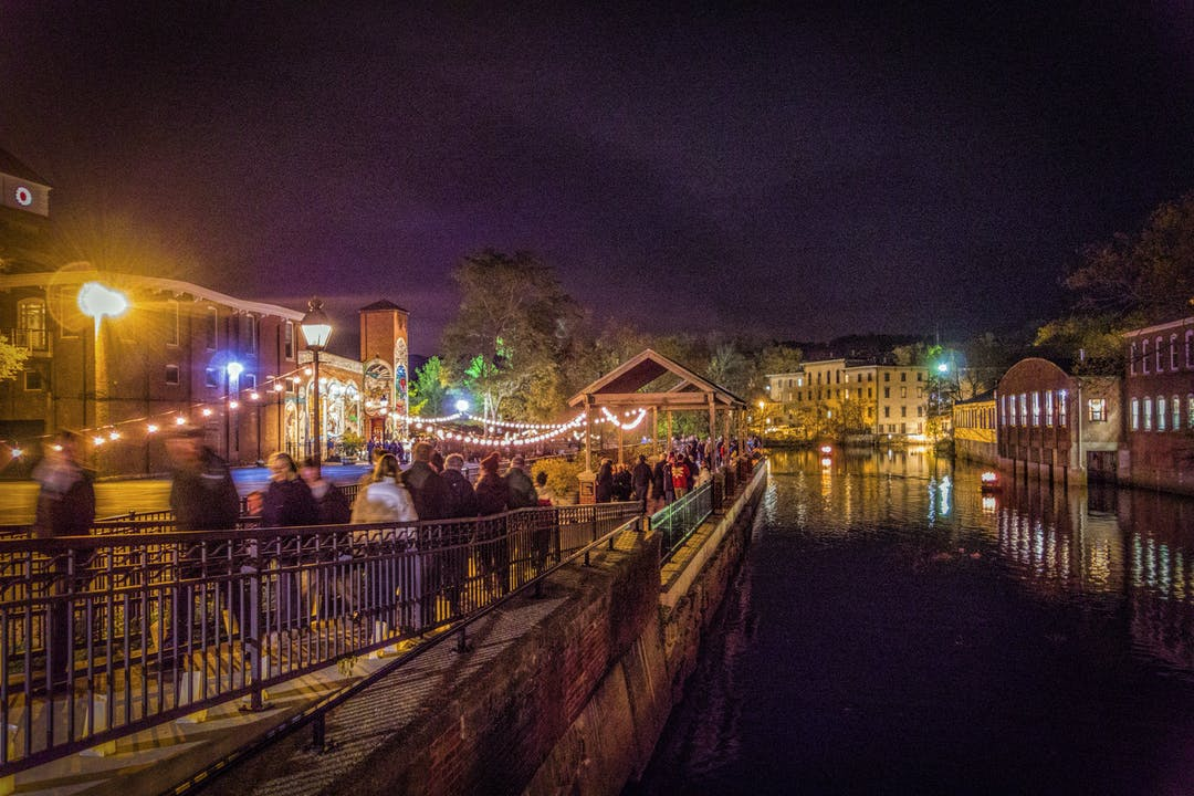 Ipswich riverfront illuminated at night with multicolor lights during community celebration